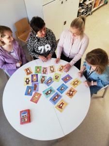 neljä naista pyöreän pöydän ääressä, keskustelee, pöydällä kuvakorttejaä