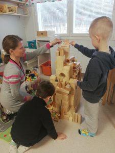 Päiväkodissa ohjaaja ja kaksi lasta rakentavat tornia palikoista